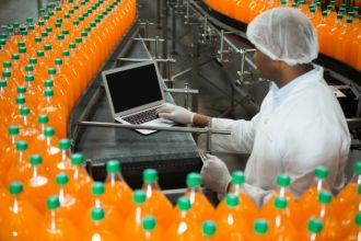 male-worker-using-laptop-amidst-production-line-juice-factory (1)